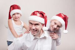 Happy children and man in santa hat Royalty Free Stock Image