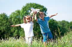 Happy children on meadow. Happy boy and little girl with plane on a meadow in a sunny day Royalty Free Stock Photography
