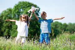Happy children on meadow. Happy boy and little girl with plane on a meadow in a sunny day Stock Photography