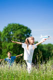 Happy children on meadow. Happy boy and little girl with plane on a meadow in a sunny day Stock Image