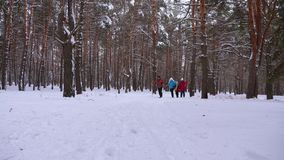Happy children and mom and dad run with the children in the winter forest. parents play with children in a snowy park in. Winter. happy family walks in stock photo