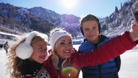 Happy children and mother making selfie by mobile phone, ice skating stock footage