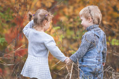 Happy children outdoor at fall season, holding hands. Has date Stock Photos