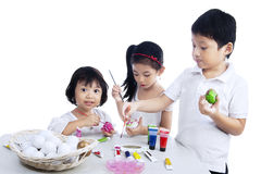 Happy children painting easter eggs Royalty Free Stock Images