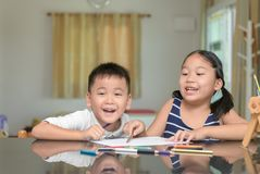 Happy children are painting pictures with colorful pencils royalty free stock photography