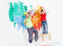 Happy children painting wall with colours Royalty Free Stock Photo