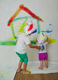 Happy children painting wall at home Royalty Free Stock Photo