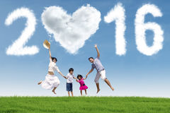 Happy children and parents celebrate new year. Two children jumping on the meadow with their parents under cloud shaped numbers 2016 Royalty Free Stock Photos
