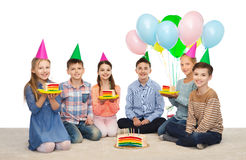 Happy children in party hats with birthday cake Royalty Free Stock Image