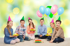 Happy children in party hats with birthday cake Royalty Free Stock Images