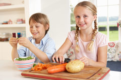 Happy children peeling vegetables in kitchen Royalty Free Stock Images