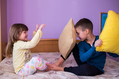 Happy children in a pillow fight. Brother and sister having fun in a pillow fight. Little boy is holding a pillow, while the girl  hits him with her pillow. Both Stock Photography
