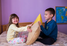 Happy children in a pillow fight. Brother and sister having fun in a pillow fight. Little boy is holding a pillow, while the girl  hits him with her pillow. Both Royalty Free Stock Photography