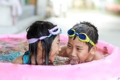 Happy children in pink rubber pool, Stock Photo