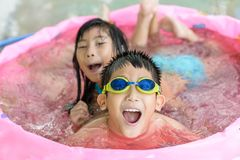 Happy children in pink rubber pool, Stock Photography