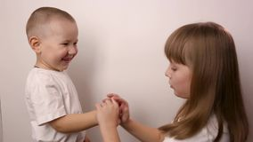 Happy children play game rock paper scissor on white background, smile and laugh stock video