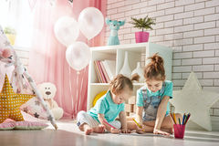 Happy children play. Little children girls draw with colored pencils indoors. Funny lovely children having fun in children room. Sisters playing together Stock Photos
