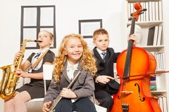 Happy children play musical instruments together. Happy children playing musical instruments together while sitting inside musical school Stock Images