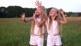 Happy children play whits blowing bubbles at summerfield. Happy children play whits blowing bubbles stock footage
