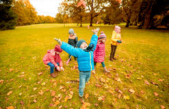 Happy children playing with autumn leaves in park Stock Photography