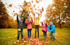 Happy children playing with autumn leaves in park Stock Photos