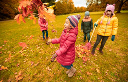 Happy children playing with autumn leaves in park Stock Photo