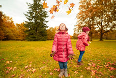 Happy children playing with autumn leaves in park Stock Images