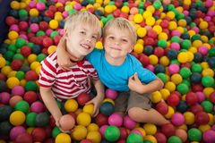 Happy children playing in ball pool Stock Photos