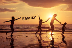 Happy children playing on the beach at the sunset time. Royalty Free Stock Image