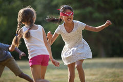 Happy children playing blind man`s buff. In summer at a birthday party Stock Photo