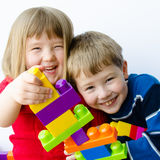 Happy children playing with blocks. Close-up of two happy playful children building a tower with colorful plastic blocks Royalty Free Stock Photography