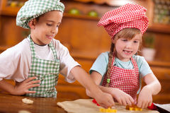 Happy children playing chef in the kitchen Stock Photos
