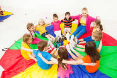 Happy children playing circle games with teacher. Big group of happy children sitting in a circle with nursery teacher, hugging and playing games Stock Photography