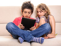 Happy children playing digital tablet Stock Images
