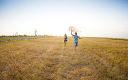 Happy children playing with flying kite on the summer field Stock Photo