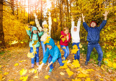 Happy children playing with flying leaves Stock Image