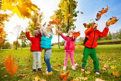 Happy children playing with flying leaves in park Royalty Free Stock Photos