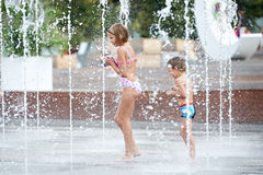 Happy children playing in a fountain stock photo