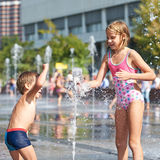 Happy children playing in a fountain Royalty Free Stock Images