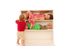 Happy children playing on fun kids bookshelf Stock Photos