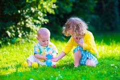 Happy children playing in the garden with toy balls. Children playing in the garden. Toddler kid and little baby play outdoors in summer. Girl and boy with toy royalty free stock images