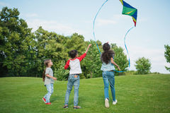 Happy children playing with kite on green grass in park stock photography
