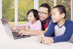 Happy children playing laptop with dad Stock Photo