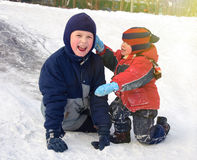 Happy children playing on a little snowy hill. Royalty Free Stock Images