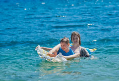 Happy Children Playing with Mattress at Sea Royalty Free Stock Photos