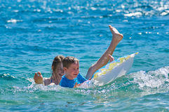 Happy Children Playing with Mattress at Sea Stock Photography