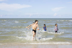 Happy Children playing in the Ocean Stock Images
