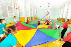 Happy children playing parachute game in gym royalty free stock photography