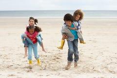 Happy children playing piggyback on beach. Having fun stock images