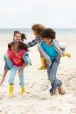 Happy children playing piggyback on beach. Having fun royalty free stock photography